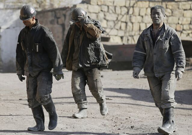 Miners walk at a coal mine from the state-owned Longmay Group on the outskirts of Jixi, in Heilongjiang province, China, October 24, 2015
