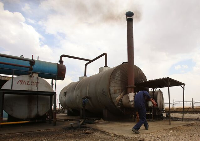 A man works on cauldron in the Rmeilane oil field in Syria's northern eastern Hasakeh province on July 15, 2015