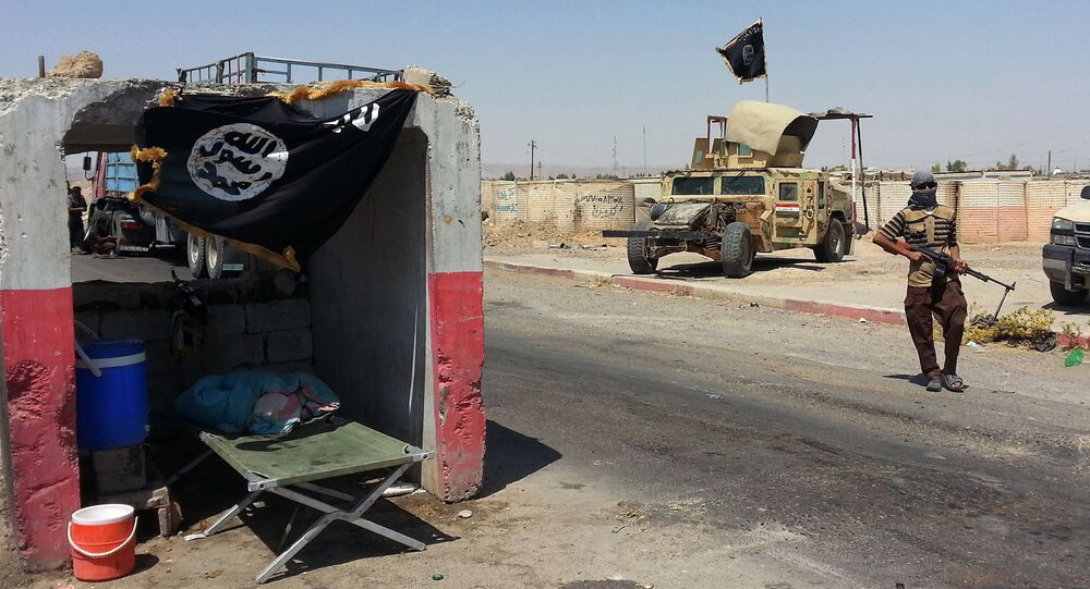 An ISIL militant stands with a captured Iraqi Army Humvee at a checkpoint outside Beiji refinery, some 250 kilometers (155 miles) north of Baghdad, Iraq, Thursday, June 19, 2014