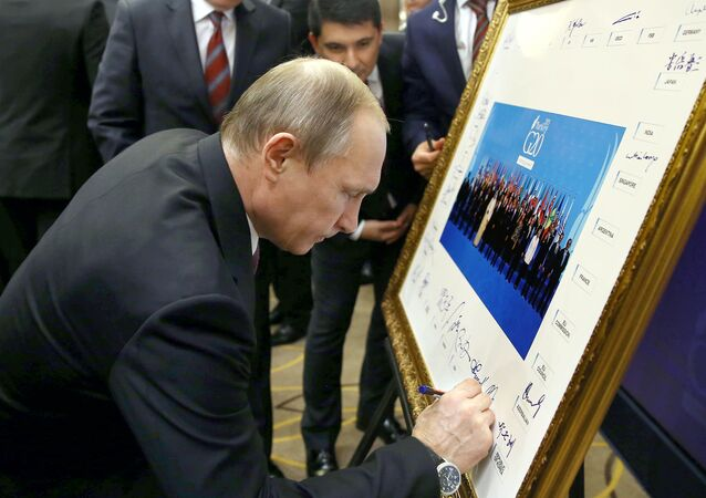 Russian President Vladimir Putin signs a print of the G20-Turkey family photo at the Group of 20 (G20) summit, in the Mediterranean resort city of Antalya, on November 15, 2015