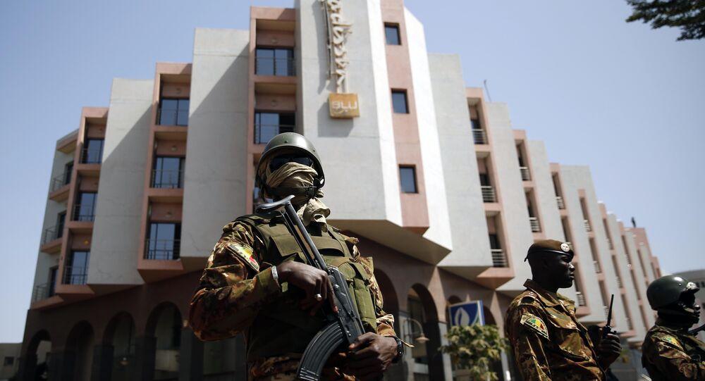 Tight security surrounds Malian President Ibrahim Boubacar Keita as he visits the Radisson Blu hotel in Bamako, Mali, Saturday, Nov. 21, 2015