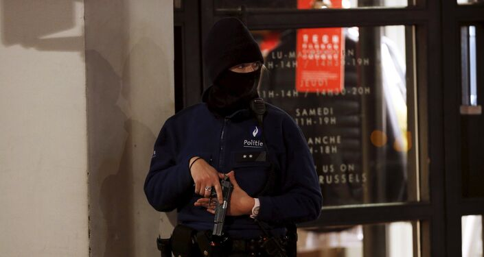 A Belgian police officer takes position along a street during a continued high level of security following the recent deadly Paris' attacks, in Brussels
