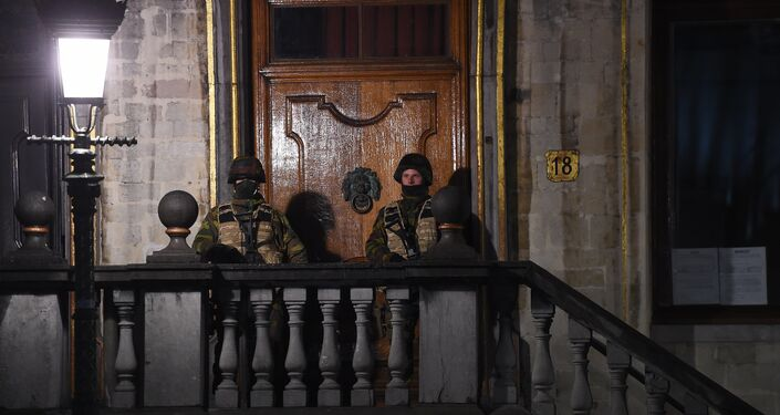 Belgian soldiers stand guard as a reported police intervention takes place around the Grand Place central square in Brussels on November 22, 2015.