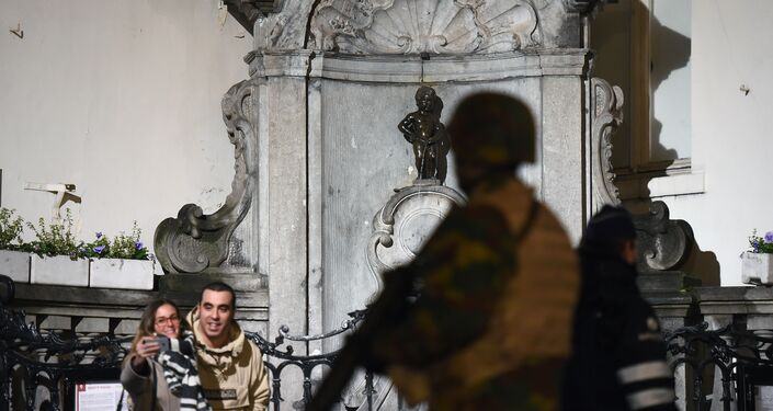 A soldier patrols around a security perimeter next to tourists taking a photo of the Manneken Pis statue, as a reported police intervention takes place, in Brussels on November 22, 2015.