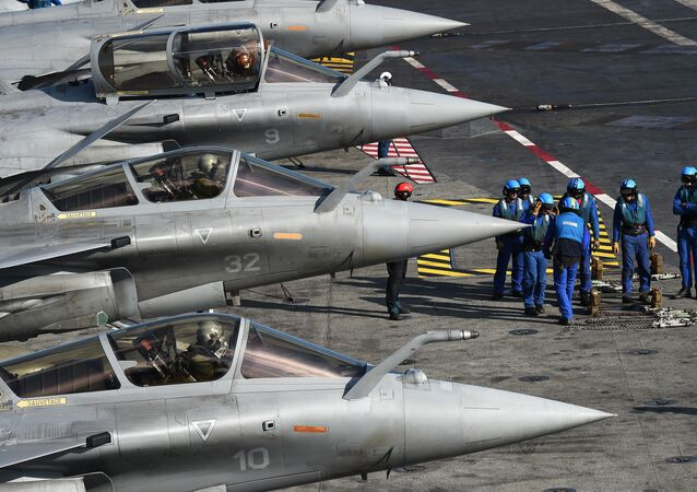 French navy soldiers prepare French Rafale jet fighters on the flight deck of the French Charles-de-Gaulle aircraft carrier on November 22, 2015 in the eastern Mediterranean Sea