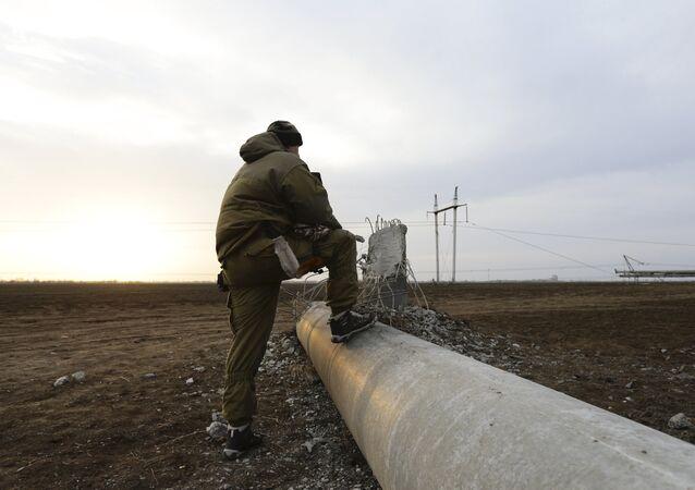 A man steps on a damaged electrical pylon near the village of Chaplynka in Kherson region, Ukraine, November 22, 2015