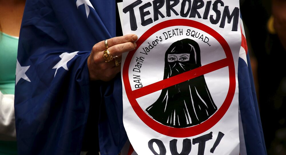 A supporter of the anti-Islam group Reclaim Australia with an Australian national flag drapped around him, holds a placard during a rally in central Sydney, Australia, November 22, 2015