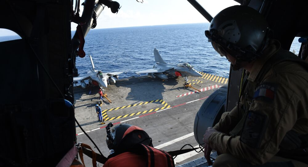 French navy technicians work on the flight deck on the aircraft carrier Charles-de-Gaulle, in eastern Mediterranean sea, on November 21, 2015
