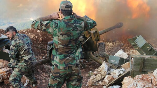 In this photo taken on Saturday, Oct. 10, 2015, Syrian army personnel fire a cannon in Latakia province, about 12 miles from the border with Turkey in Syria - Sputnik International