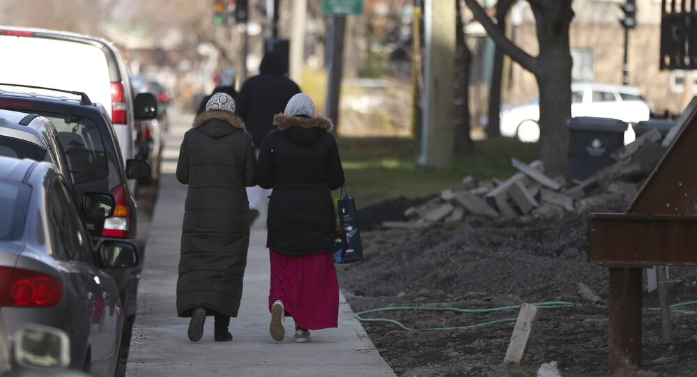 Two women walk down a street in Montreal, November 18, 2015