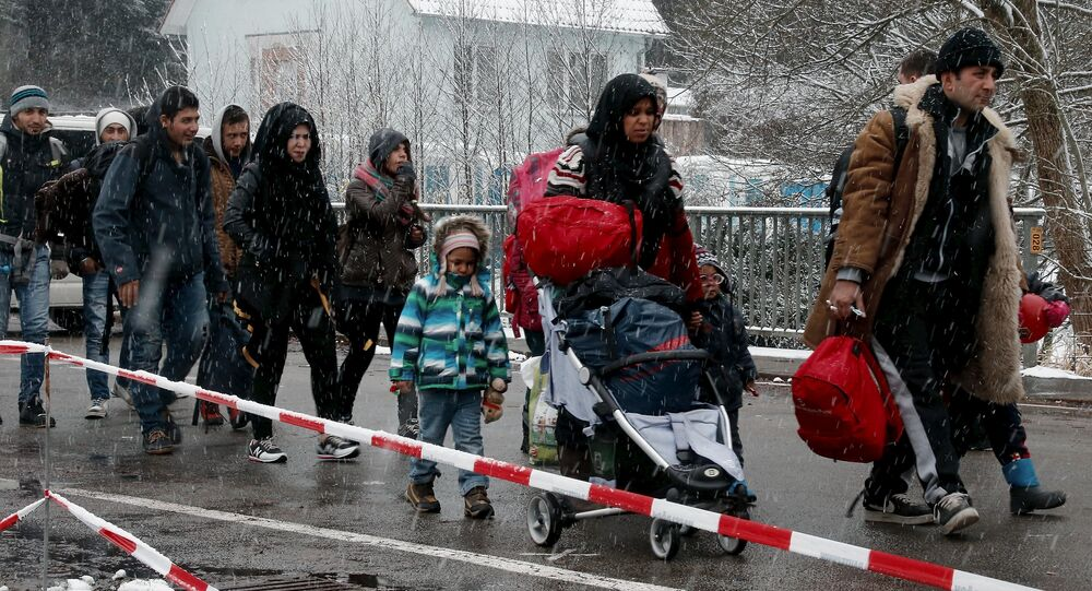 Migrants stay in queue during heavy snowfall before passing Austrian-German border in Wegscheid in Austria, near Passau November 22, 2015