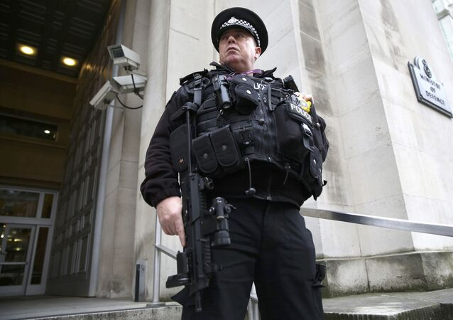 An armed police officer stands guard outside of the Ministry of Defence in London, Britain November 18, 2015