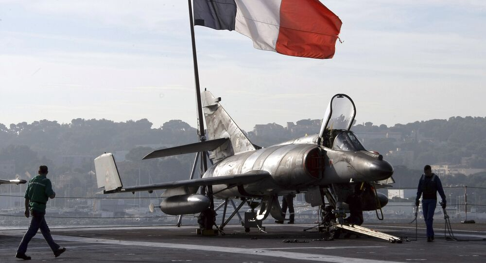 French sailors walk by a Super-Etendard jet fighter on the deck of France's nuclear-powered aircraft carrier Charles de Gaulle before it leaves its home port of Toulon in southern France, 18 November 2015