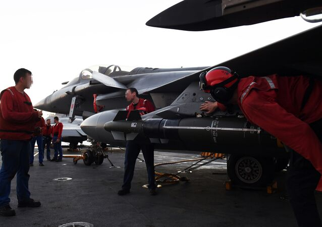 French navy engineers install a missile on a French Rafale fighter aircraft aboard the French Charles-de-Gaulle aircraft carrier, on November 23, 2015 at the eastern Mediterranean sea, as part of operation Chammal in Syria and Irak against the Islamic State group