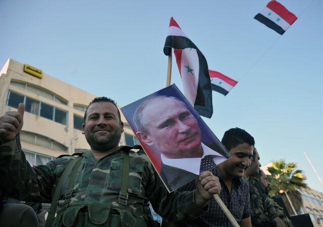 Syrian Arab Army troops take part in a rally in Tarus in support of the Russian Aerospace Force operation in Syria