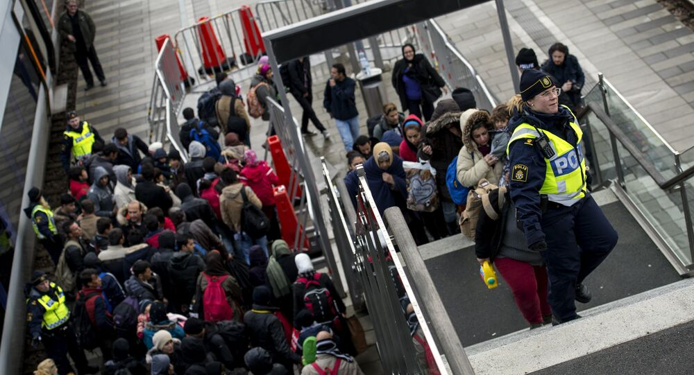 Police organize the line of refugees at on the stairway leading up from the trains arriving from Denmark at the Hyllie train station outside Malmo, Sweden, November 19, 2015.