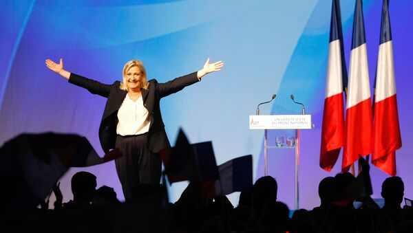 France's far-right National Front president Marine Le Pen, center, surrounded by members, waves to supporters after her speech during their meeting in Marseille, southern France, Saturday, Sept. 6, 2015. - Sputnik International