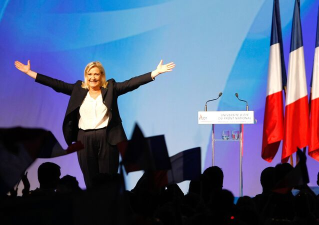 France's far-right National Front president Marine Le Pen, center, surrounded by members, waves to supporters after her speech during their meeting in Marseille, southern France, Saturday, Sept. 6, 2015.