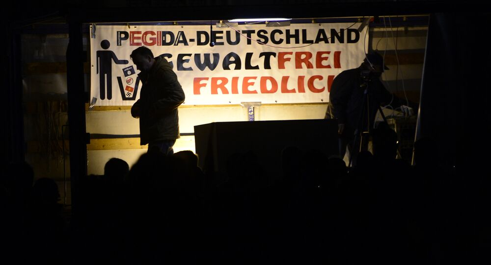 Pegida founder Lutz Bachmann is silhouetted during a demonstration of PEGIDA (Patriotic Europeans against the Islamization of the West) in Dresden, eastern Germany, Monday, Nov. 2, 2015.