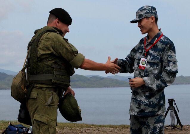 Russian and Chinese servicemen shake hands