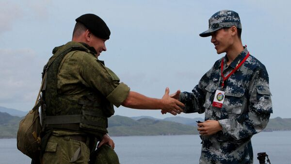 Russian and Chinese servicemen shake hands during the Russian-Chinese drill Naval Interaction-2015 at the Klerk testing grounds in Russia's Primorye Territory. - Sputnik International