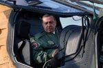 In this Tuesday, June 10, 2014 photo, Turkish Prime Minister Recep Tayyip Erdogan sits in the pilot's sesat during a presentation for the Turkish-made military attack helicopter, T129 ATAK, outside Ankara, Turkey