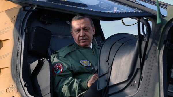 Turkish Prime Minister Recep Tayyip Erdogan sits in the pilot's seat during a presentation for the Turkish-made military attack helicopter, T129 ATAK, outside Ankara, Turkey. Picture taken 10 June 2014.  - Sputnik International