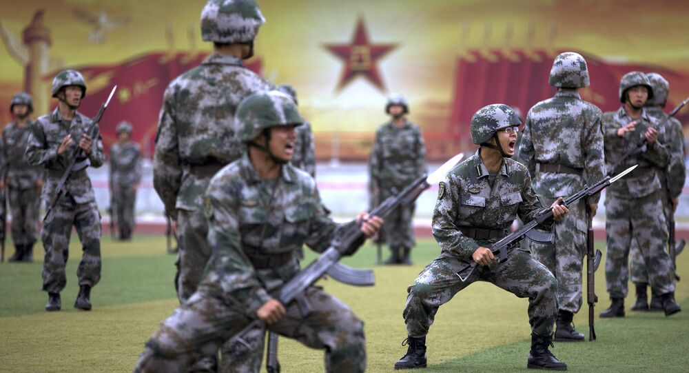 Chinese People's Liberation Army cadets shout as they take part in a bayonet drills at the PLA's Armoured Forces Engineering Academy Base, on the outskirts of Beijing, China, July 22, 2014