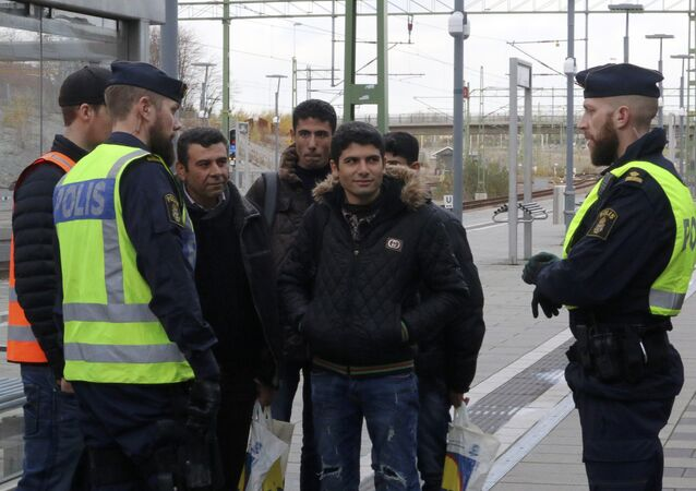 Swedish police officers speak to a group of people at the Hyllie train station near Malmo, Sweden, November 12, 2015.