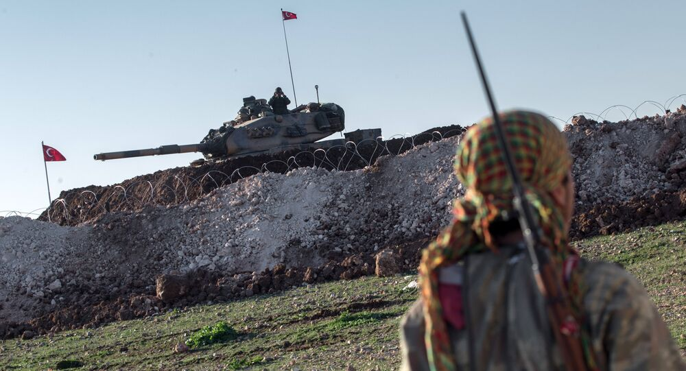 A Syrian Kurdish militia member of YPG patrols near a Turkish army tank as Turks work to build a new Ottoman tomb in the background in Esme village in Aleppo province, Syria, Sunday, Feb. 22, 2015