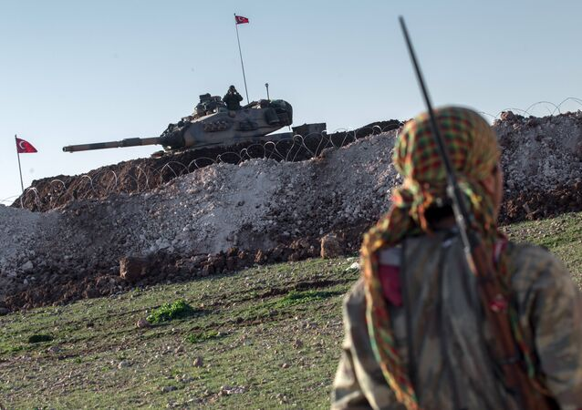 File Photo: A Syrian Kurdish militia member of YPG patrols near a Turkish army tank as Turks work to build a new Ottoman tomb in the background in Esme village in Aleppo province, Syria, Sunday, Feb. 22, 2015