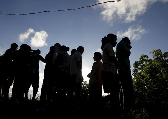 People stand near at a crime scene where seven men were killed, in Tegucigalpa, Honduras