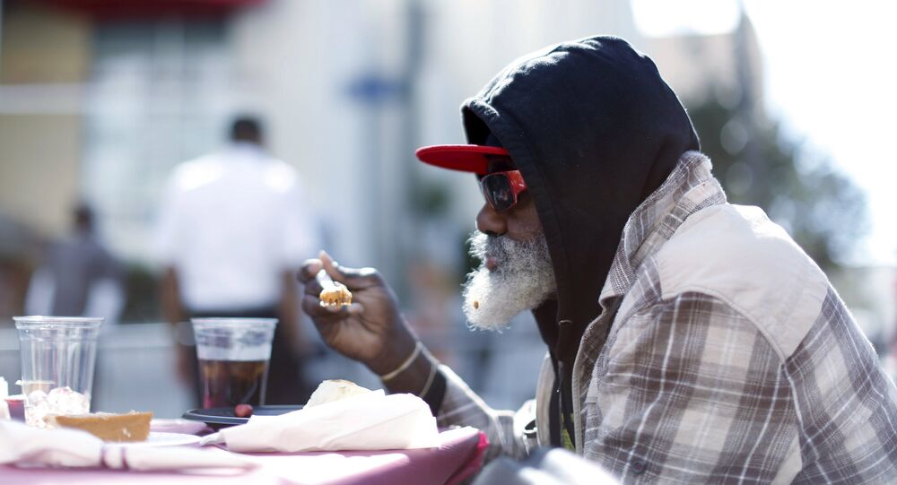 A man eats an early Thanksgiving meal served to the homeless.