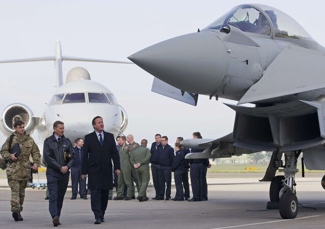 Britain's Prime Minister David Cameron (3rd L) looks at an RAF Eurofighter Typhoon fighter jet during his visit to Royal Air Force station RAF Northolt in London, Britain November 23, 2015.