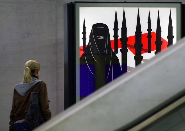 A woman passes by a campaign poster of the far-right Swiss People's Party depicting a woman wearing a burqa against a background of a Swiss flag upon which several minarets resembling missiles on October 26, 2009 at the central station in Zurich.