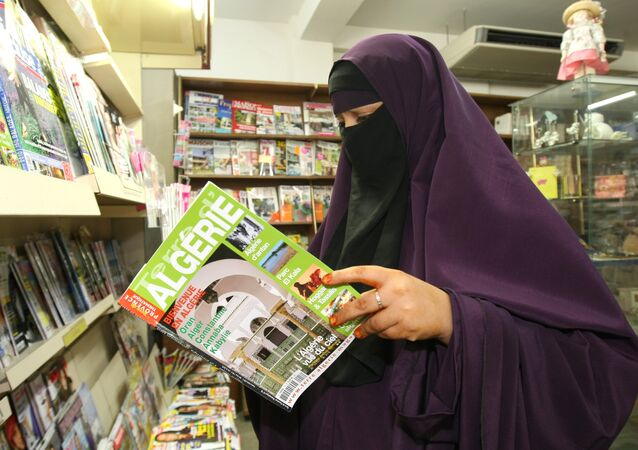A woman wears a niqab, as she reads a magazine in a shop
