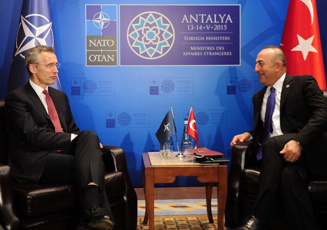 Turkish Foreign Minister Mevlut Cavusoglu (R) speaks with NATO Secretary General Jens Stoltenberg (L) during a meeting on May 12, 2015 in Antalya