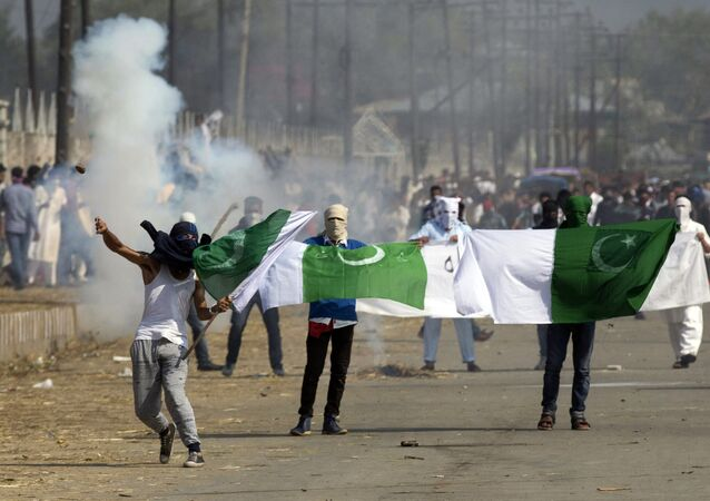 Masked Kashmiris hold the national flag of Pakistan and a banner displaying militant leaders of the Hizb-ul Mujahedeen during a protest outside Eidgha, a prayer ground, in Srinagar, Indian controlled Kashmir, Friday, Sept. 25, 2015.