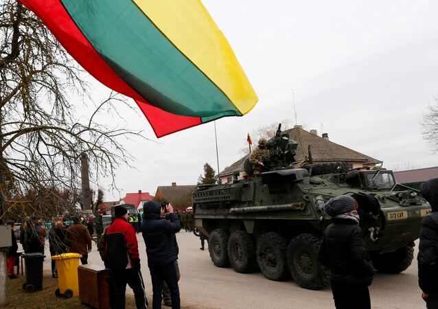 Local residents watch as a members of US Army's 2nd Cavalry Regiment ride on an armored vehicle during the ''Dragoon Ride'' military exercise, in Salociai some 178 kms (110 miles) north of the capital Vilnius, Lithuania, Monday, March 23, 2015.
