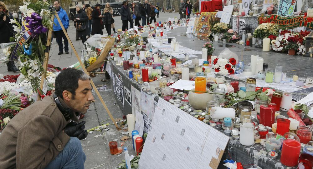 """A man reads messages at the Place de la Republique in Paris, Friday, Nov. 27, 2015. A subdued France paid homage Friday to those killed two weeks ago in the attacks that gripped Paris in fear and mourning, honoring each of the 130 dead by name as the president pledged to """"destroy the army of fanatics"""" who claimed so many young lives."""