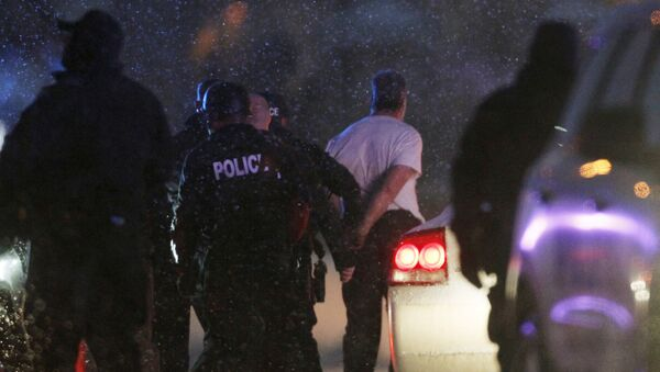 The handcuffed suspected gunman at the Planned Parenthood clinic is moved to a police vehicle in Colorado Springs, Colorado - Sputnik International
