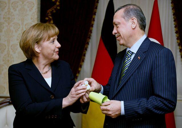 German Chancellor Angela Merkel, left, and Turkish President Recep Tayyip Erdogan exchange gifts before their talks