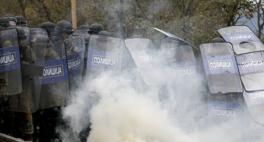Macedonian police officers try to take cover from tear gas thrown back by a stranded migrant, as minor clashes broke out during a protest against the building of a metal fence at the Greek-Macedonian borders near the village of Idomeni, Greece November 28, 2015