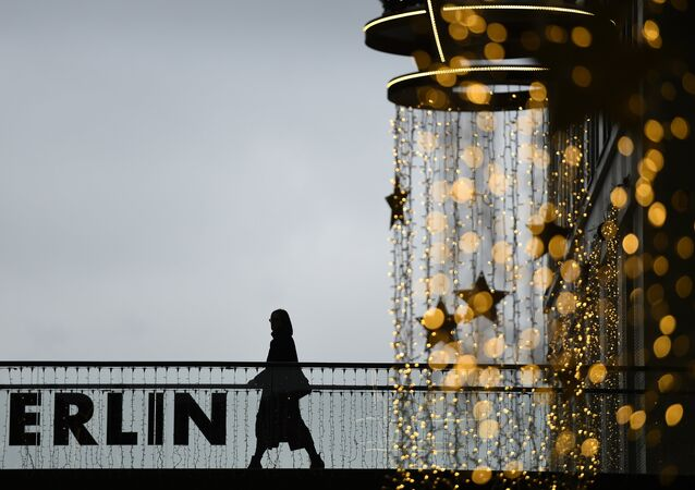 A woman walks past a Christmas decoration at a shopping mall in Berlin November 26, 2015
