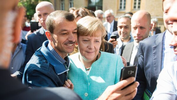 Asylum seeker (C, L) takes a selfie picture with German Chancellor Angela Merkel (C, R) following Merkel's visit at a branch of the Federal Office for Migration and Refugees and a camp for asylum-seekers in Berlin on September 10, 2015. - Sputnik International