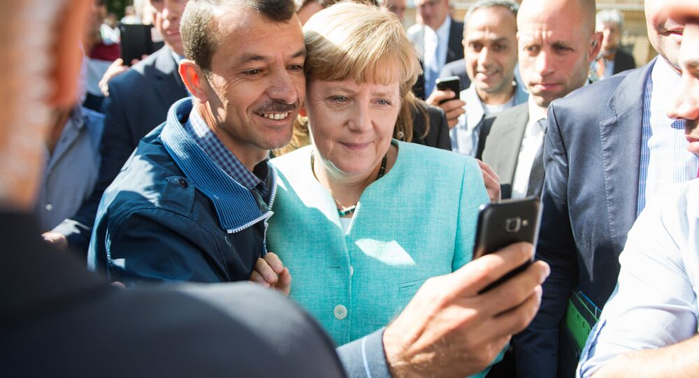 Asylum seeker (C, L) takes a selfie picture with German Chancellor Angela Merkel (C, R) following Merkel's visit at a branch of the Federal Office for Migration and Refugees and a camp for asylum-seekers in Berlin on September 10, 2015