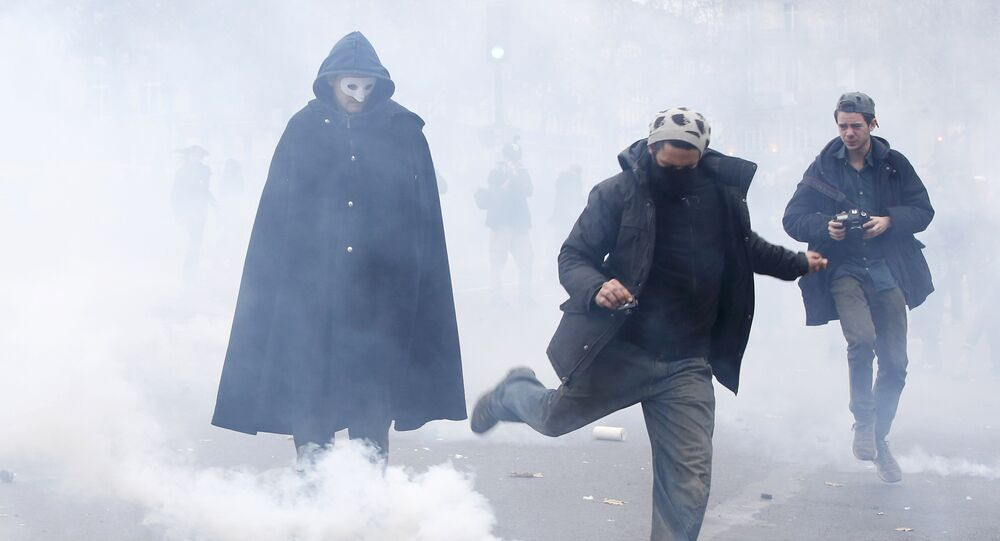 A demonstrator kicks a tear gas canister during clashes with CRS riot police near the Place de la Republique after the cancellation of a planned climate march following shootings in the French capital, ahead of the World Climate Change Conference 2015 (COP21), in Paris, France, November 29, 2015