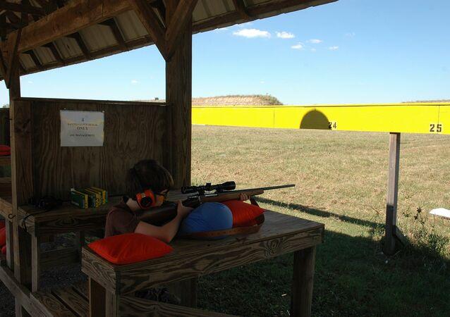 A boy practices shooting at a gun range