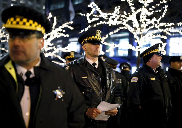 Police officers watch protesters during a demonstration in reaction to the fatal shooting of Laquan McDonald in Chicago, Illinois, November 27, 2015