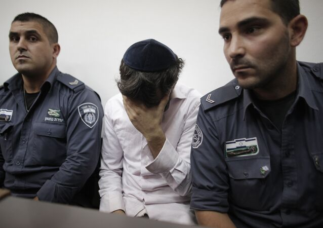 Yosef Haim Ben-David (C) the 29-year-old Israeli prime suspect, who was charged along with two minors for the abduction and murder of the Palestinian teenager Mohammed Abu Khder, covers his face as he sits in the courtroom of the Jerusalem district court during his trial on August 6, 2014